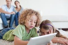 Bambini in giovane età che per mezzo di un calcolatore del ridurre in pani Immagini Stock