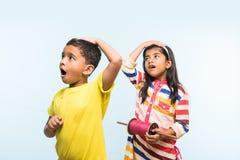 2 bambini indiani che pilotano aquilone, uno che giudica spindal o chakri Immagini Stock
