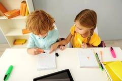Bambini intelligenti che assorbono taccuino all'interno Immagine Stock Libera da Diritti