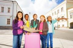 Bambini internazionali che stanno con la mappa ed i bagagli Immagini Stock