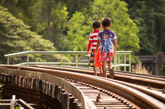 Bambini locali che camminano sulla ferrovia in Kanchanaburi Fotografia Stock Libera da Diritti