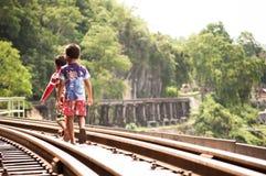 Bambini locali che camminano sulla ferrovia in Kanchanaburi Immagine Stock Libera da Diritti