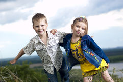 Bambini in modo divertente su una priorità bassa un paesaggio Immagini Stock Libere da Diritti