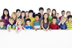 Bambini Multi-etnici del gruppo che tengono concetto vuoto del tabellone per le affissioni Fotografia Stock