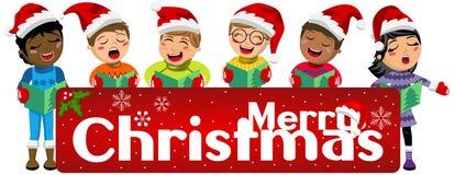 Bambini multiculturali che indossano l'insegna della canzone di Natale di canto del cappello di natale isolata Immagini Stock Libere da Diritti