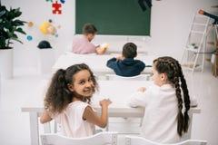 Bambini multietnici svegli che si siedono agli scrittori della scuola e che studing nell'aula Fotografia Stock