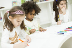 Bambini multirazziali che assorbono la stanza dei giochi Fotografia Stock Libera da Diritti