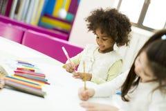 Bambini multirazziali che assorbono la stanza dei giochi Fotografie Stock