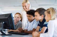 Bambini nella classe del computer con l'insegnante Immagini Stock