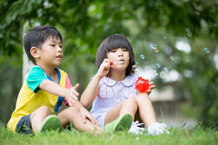 Bambini nelle bolle di sapone di salto del parco Fotografie Stock Libere da Diritti