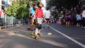 Bambini non identificati del pattinaggio a rotelle della città di Calcutta sulla strada bloccata, India stock footage