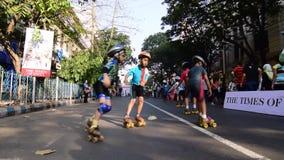 Bambini non identificati del pattinaggio a rotelle della città di Calcutta sulla strada bloccata, India archivi video