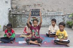 Bambini non privilegiati che studiano istruzione elementare a scuola aperta Fotografie Stock