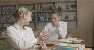 Bambini o due ragazze felici che imparano e che fanno compito nell'aula della scuola video d archivio