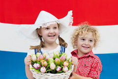 Bambini olandesi con i fiori del tulipano e la bandiera olandese Immagine Stock