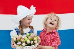 Bambini olandesi con i fiori del tulipano e la bandiera olandese Immagini Stock