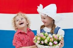 Bambini olandesi con i fiori del tulipano e la bandiera olandese Immagini Stock Libere da Diritti
