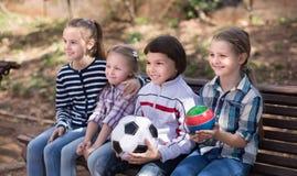 Bambini ordinari nel parco su un banco in autunno Immagini Stock Libere da Diritti
