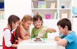 Bambini osservando un progetto del laboratorio di scienza a casa Immagini Stock