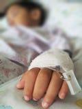 Bambini pazienti in ospedale con il dispositivo di venipunzione salino, sfuocatura e Fotografia Stock