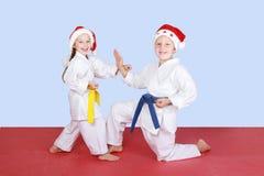 Bambini piccoli nel karatè di esercizio della vettura di Santa Claus dei cappucci Fotografia Stock Libera da Diritti