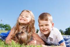 Bambini positivi che giocano con il cane Fotografia Stock Libera da Diritti