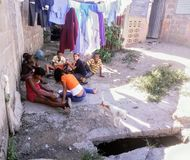 Bambini poveri che giocano sulla terra accanto ad uno sbocco Immagini Stock Libere da Diritti