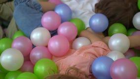 Bambini prescolari caucasici di risata che giocano nel multi stagno colorato della palla asilo archivi video