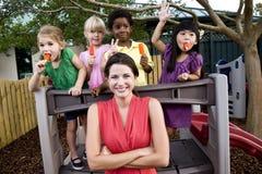 Bambini prescolari sul campo da giuoco con l'insegnante Fotografia Stock