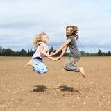 Bambini - ragazze che saltano sul campo Fotografie Stock