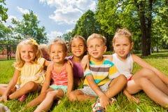 Bambini, ragazzi e ragazze sul prato inglese in parco Immagine Stock