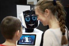 Bambini ragazzo e conversazione della ragazza, giocante con un robot di androide Fotografia Stock Libera da Diritti