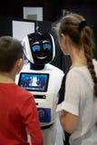 Bambini ragazzo e conversazione della ragazza, giocante con un robot di androide Fotografie Stock