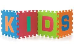 Bambini - segno con le lettere di puzzle di alfabeto su bianco Fotografie Stock
