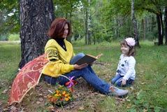 Bambini sorridenti all'aperto vacatireading h della donna della figlia del padre di divertimento della natura di amore del bambin Fotografia Stock