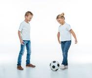 Bambini sorridenti che giocano con il pallone da calcio Fotografie Stock Libere da Diritti