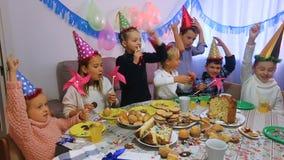 Bambini sorridenti che hanno celebrazione del compleanno dei friend's durante la cena archivi video