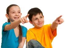 Bambini sorridenti che indicano in avanti immagine stock