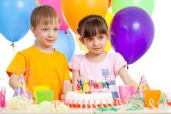 Bambini sorridenti con la torta di compleanno e gli impulsi di colore Immagine Stock