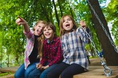 Bambini sorridenti divertendosi al campo da giuoco Bambini che giocano all'aperto di estate Adolescenti che guidano su un'oscilla Immagine Stock