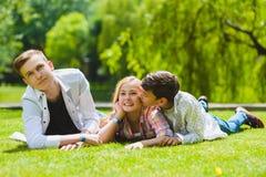 Bambini sorridenti divertendosi all'erba Bambini che giocano all'aperto di estate gli adolescenti comunicano all'aperto Fotografia Stock Libera da Diritti