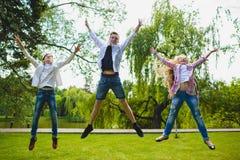 Bambini sorridenti divertendosi e saltando all'erba Bambini che giocano all'aperto di estate gli adolescenti comunicano all'apert Immagini Stock