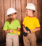 Bambini sorridenti in elmetti protettivi con gli strumenti sul gabinetto di legno del fondo immagine stock