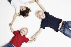 Bambini sorridenti sulle mani della holding del pavimento Fotografie Stock Libere da Diritti