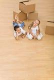 Bambini sul pavimento nella loro nuova casa Immagine Stock