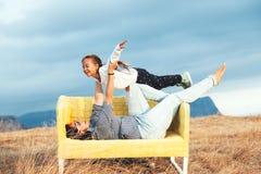 Bambini sul sofà all'aperto Fotografie Stock Libere da Diritti