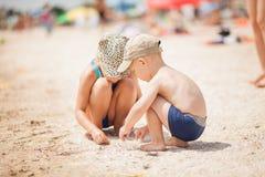 Bambini sulla spiaggia che cerca le piccole conchiglie Fotografia Stock Libera da Diritti