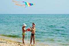 Bambini sulla spiaggia che gioca con un aquilone fotografia stock libera da diritti