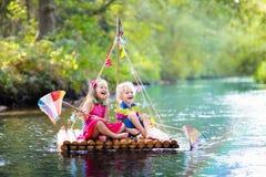 Bambini sulla zattera di legno fotografia stock