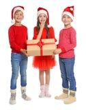 Bambini svegli in cappelli di Santa con il contenitore di regalo di Natale su fondo bianco Immagini Stock Libere da Diritti